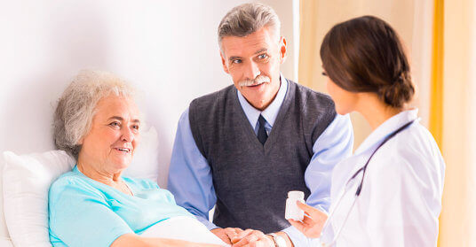 nurse talking to old couple